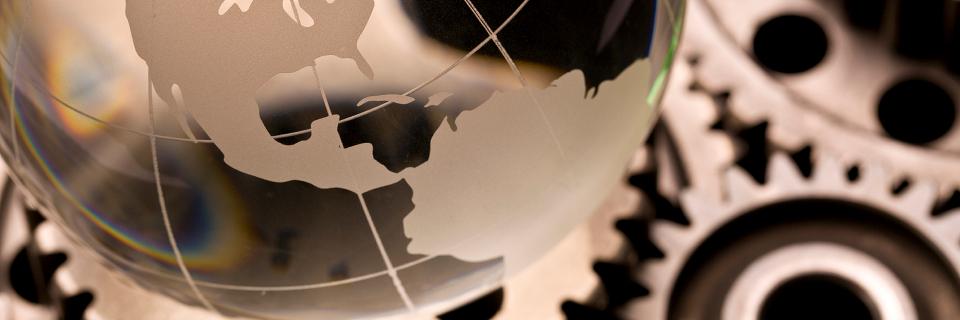 Glass globe on metal gears tinted gold,